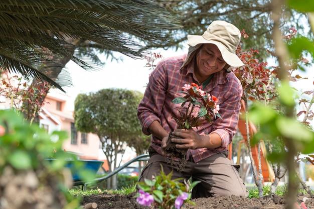 美しい緑豊かな庭園に花を植えるラテン男