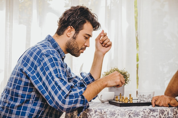 Latin man playing chess board game at home for holiday activity with his family he thinking and look serious