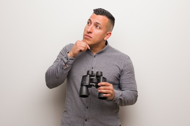 Latin man relaxed thinking about something looking at a copy space. he is holding a binoculars.
