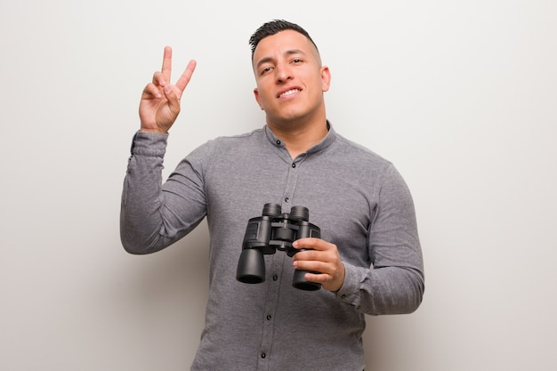 Latin man showing number two. he is holding a binoculars.
