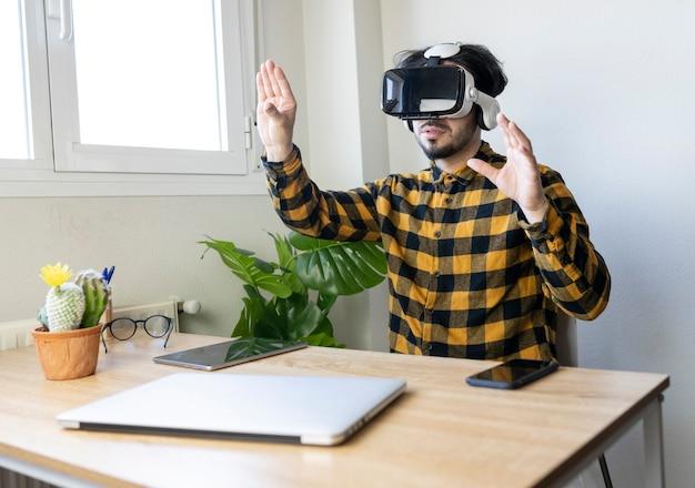 Латинский мужчина, сидящий в офисе, работает из дома в очках виртуальной реальности