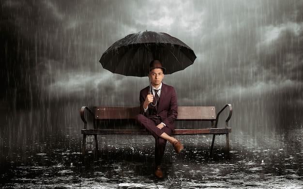 폭풍우 치는 밤의 한가운데에 우산을 들고 벤치에 앉아 있는 라틴 남자, 수평
