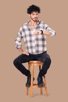 Uomo latino seduto su uno sgabello mentre controlla l'ora