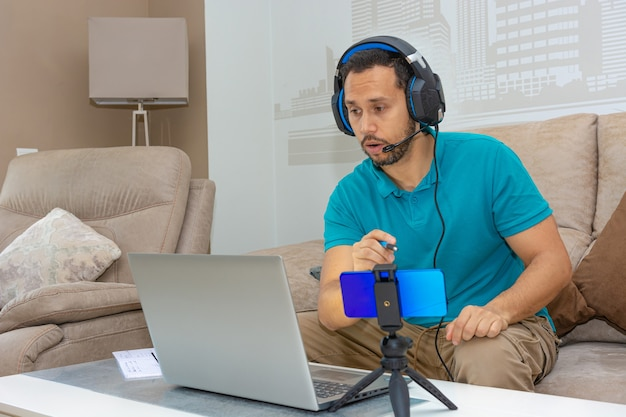 집 소파에서 온라인 과정을 수강하는 라틴 남자 (온라인 과정 및 고등 교육의 개념)