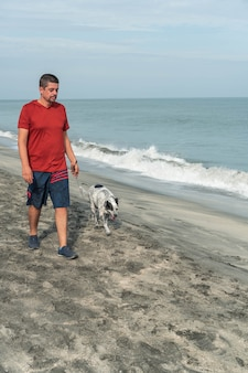 Латинский мужчина гуляет с собакой утром на пляже