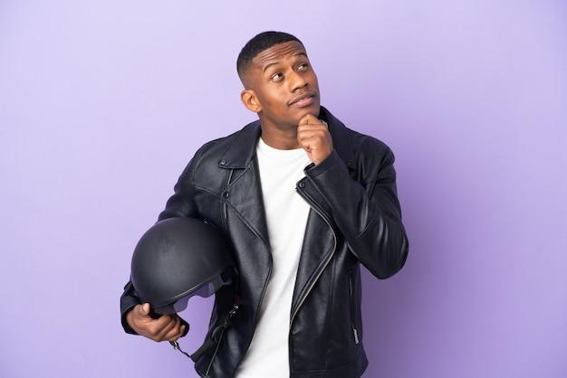 보라색에 고립 된 오토바이 헬멧을 가진 라틴 남자를 찾고