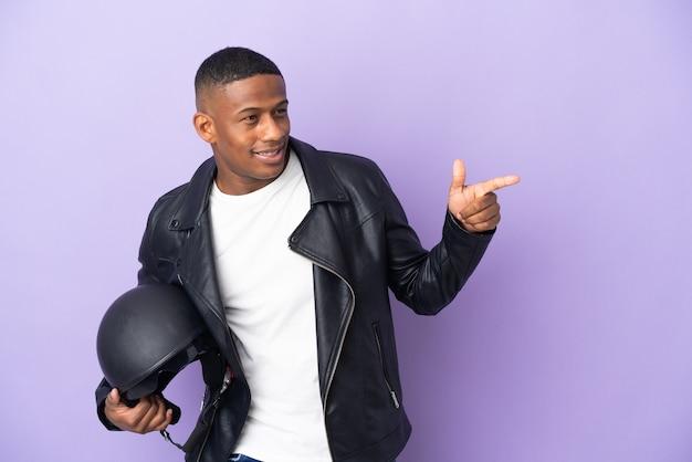 横に指を指し、製品を提示する紫色の背景に分離されたオートバイのヘルメットを持つラテン男性