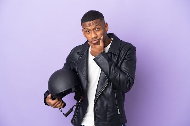Латинский мужчина в мотоциклетном шлеме изолирован на фиолетовом фоне мышления