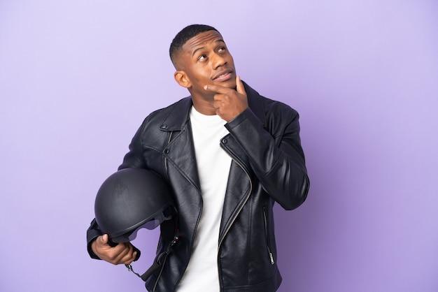 웃는 동안 찾고 보라색에 고립 된 오토바이 헬멧 라틴 남자