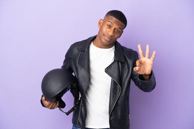 보라색 벽에 고립 된 오토바이 헬멧 라틴 남자 행복 하 고 손가락으로 세 세