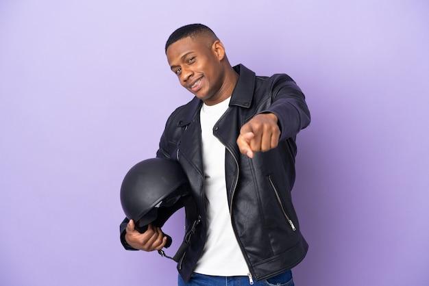 幸せな表情で正面を指す紫色の壁に分離されたオートバイのヘルメットを持つラテン男