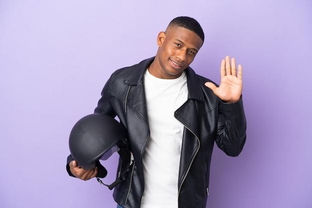 分離されたオートバイのヘルメットを持つラテン男