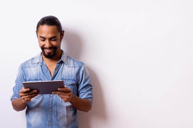 Латинский мужчина с бородой и завязанными волосами с большим отношением и улыбкой на лице думает и смотрит, держа планшет в руках, на белом фоне ... копирование пространства. концепция покупки.