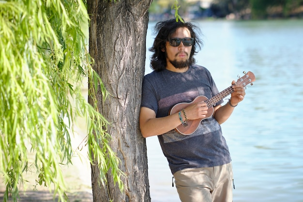 Latin man with sunglasses, plays the ukulele leaning on a tree in the background a lake.