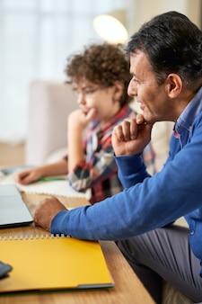 ラテン語の中年の父親が宿題をチェックし、自宅のテーブルに座ってかわいい息子、男子生徒の勉強を手伝っています。遠隔学習、家族、父性の概念