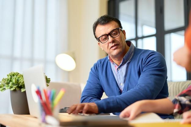 ラテン語の中年の父親が息子と一緒に机に座って、自宅での遠隔教育中に子供が勉強するのを手伝っています。オンライン教育、ホームスクーリングの概念