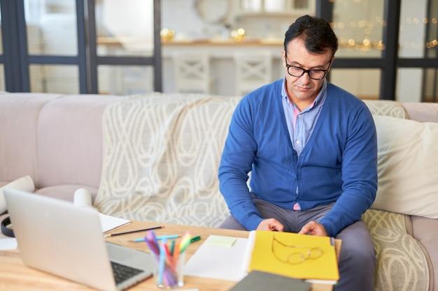 ソファに座っているラテン語の中年の父親は、自宅での遠隔教育中に子供が勉強するのを手伝いながら集中しているように見えます。オンライン教育、ホームスクーリングの概念