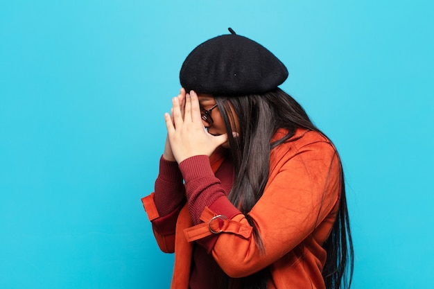 Latin woman covering eyes with hands with a sad, frustrated look of despair, crying, side view