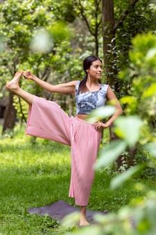 Латинская женщина делает позы йоги, хватаясь за ногу в парке на зеленой траве в розовом наряде