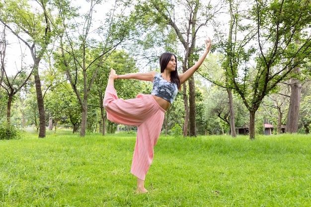 Латинская женщина делает йогаасаны в разных позах в открытом парке с травой и деревьями
