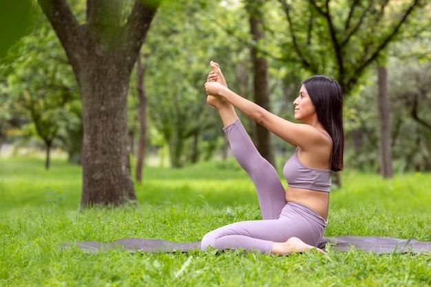 Латинская женщина делает йогаасаны в разных позах в открытом парке с травой