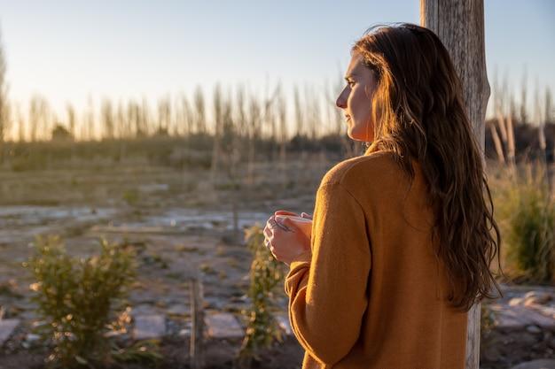 夕日を見ながらコーヒーを飲むラテン女性