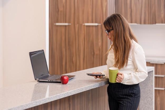 집에 있는 자신의 컴퓨터 개념을 작업하는 동안 커피를 마시는 라틴 여성