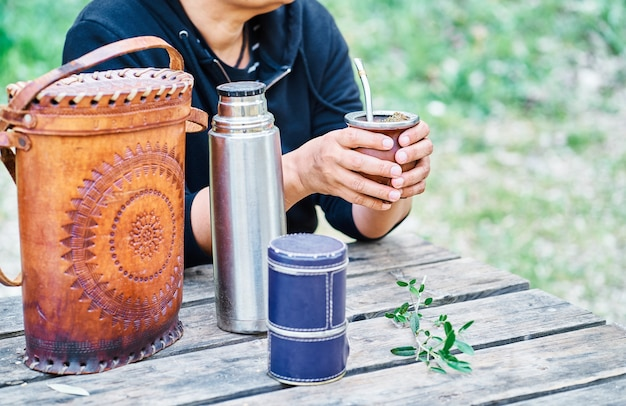 Latin woman drinking mate grass and enjoying sitting at a wooden table in the countryside