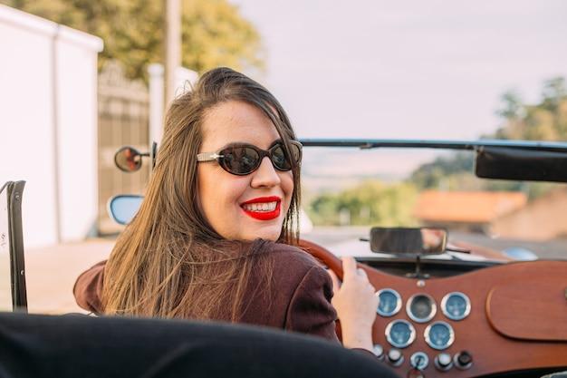 友人と一緒に旅行する古いコンバーチブル車を運転するラテン女性
