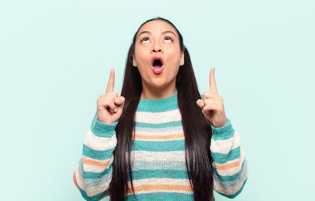 Латинская женщина чувствует благоговение и открывает рот, указывая вверх с шокированным и удивленным взглядом