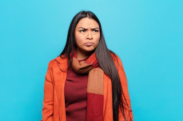 Латинская женщина смущена и сомневается, задается вопросом или пытается выбрать или принять решение