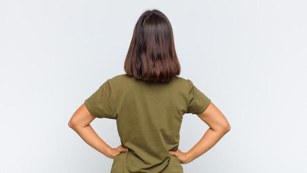 Латинская женщина, чувствуя себя растерянной или наполненной, или сомнениями и вопросами, недоумевающими, с руками на бедрах, вид сзади