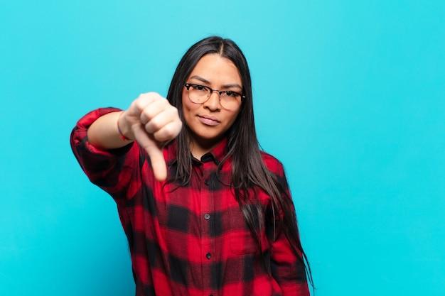 십자가, 분노, 짜증, 실망 또는 불쾌감을 느끼고 심각한 표정으로 엄지 손가락을 보여주는 라틴 여성