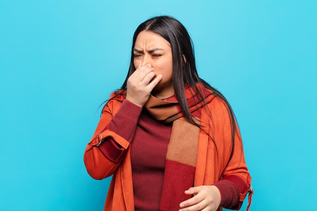 Latin woman feeling disgusted, holding nose to avoid smelling a foul and unpleasant stench