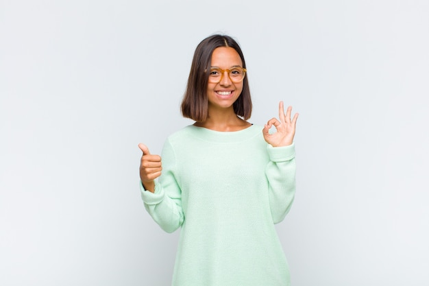 Latin woman feeling happy, amazed, satisfied and surprised, showing okay and thumbs up gestures, smiling