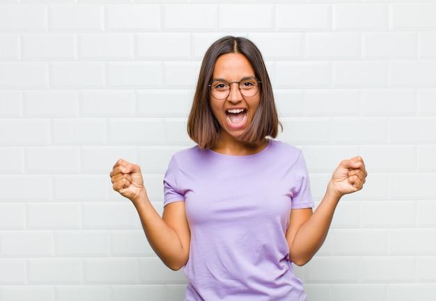 幸せ、前向き、成功を感じ、勝利、成果、または幸運を祝うラテン女性