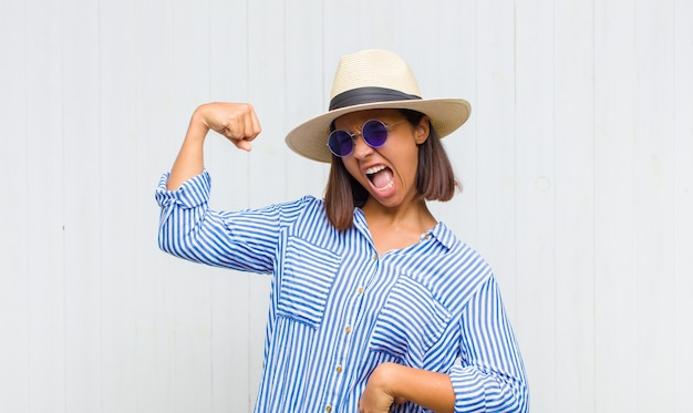 Latin woman feeling happy, satisfied and powerful, flexing fit and muscular biceps, looking strong after the gym