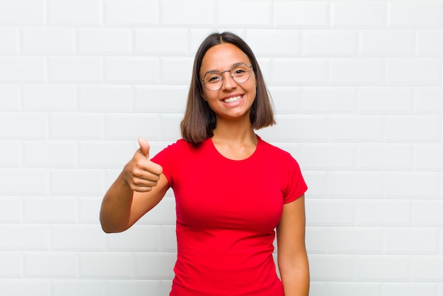 Latin woman feeling proud, carefree, confident and happy, smiling positively with thumbs up