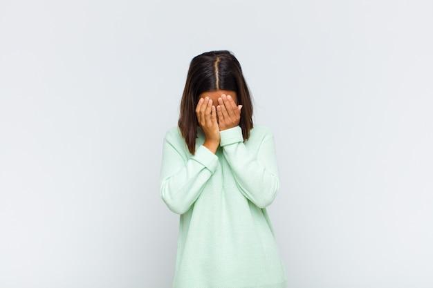 Латинская женщина чувствует себя грустной, разочарованной, нервной и подавленной, закрывает лицо обеими руками, плачет