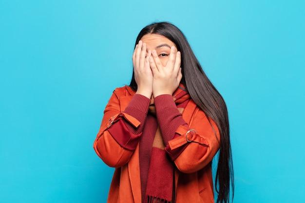 Латинская женщина чувствует страх или смущение, подглядывает или шпионит глазами, наполовину прикрытыми руками