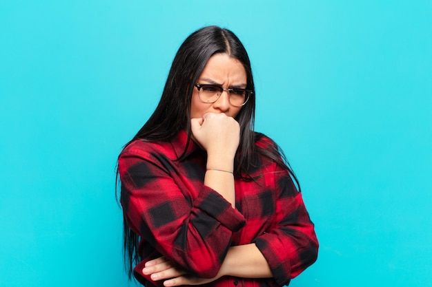 Latin woman feeling serious, thoughtful and concerned, staring sideways with hand pressed against chin