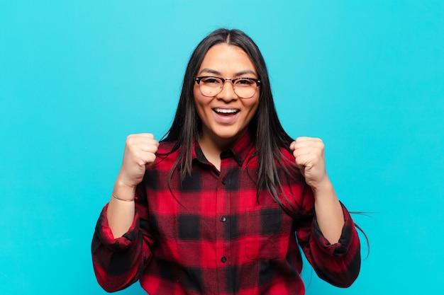 라틴 여성은 충격을 받고, 흥분하고, 행복하고, 웃고, 성공을 축하하며, 와우라고 말합니다!