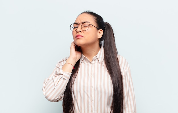 Latin woman feeling stressed, frustrated and tired, rubbing painful neck, with a worried, troubled look
