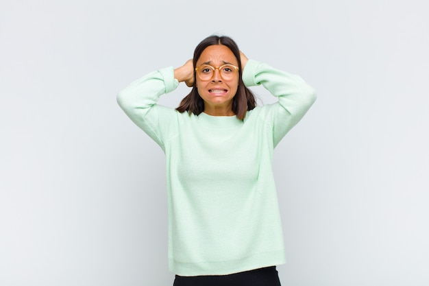 Latin woman feeling stressed, worried, anxious or scared, with hands on head, panicking at mistake