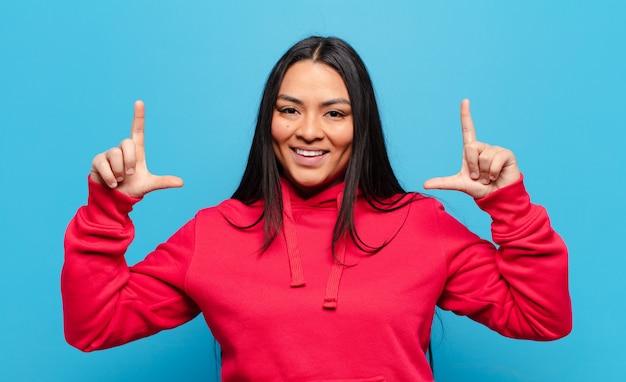 Латинская женщина, обрамляющая или очерчивающая собственную улыбку обеими руками, выглядящая позитивно и счастливой, концепция благополучия