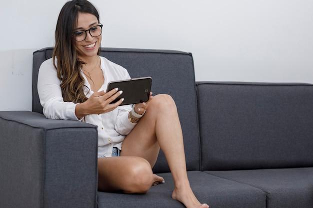 デジタルタブレットを使用して彼女のリビングルームに座っている快適な服を着たラテン女性