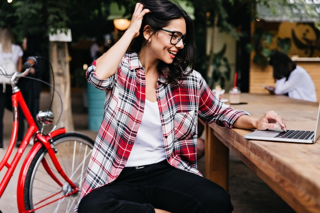 自転車の横に座っている流行の市松模様のシャツを着たラテン女性。カフェでラップトップを使用して明るいブルネットの女の子の屋外写真。