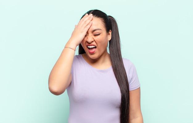 Латинская женщина смеется и хлопает по лбу, как будто говоря: «о! я забыл или это была глупая ошибка