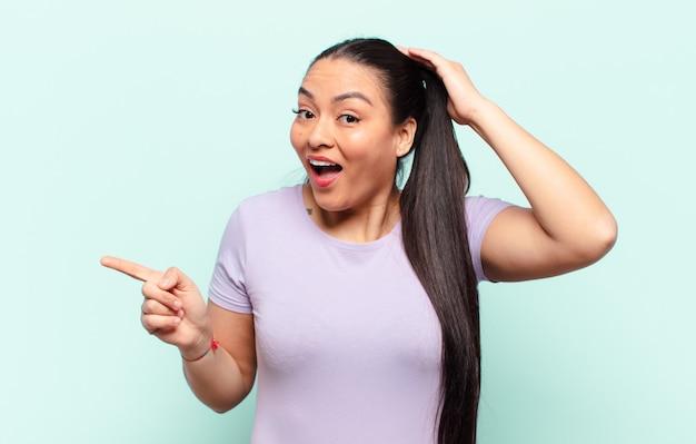 ラテン系の女性が笑い、幸せそうに見え、前向きで驚き、横方向のコピースペースを指す素晴らしいアイデアを実現
