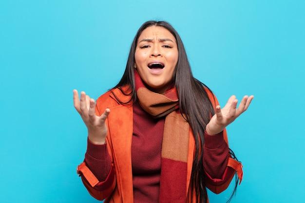 Латинская женщина выглядит отчаянной и разочарованной, напряженной, несчастной и раздраженной, кричит и кричит